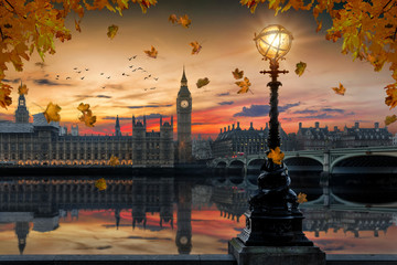 Photo sur Plexiglas Londres Herbst in London: goldener Sonnenuntergang hinter dem Westminster Palast an der Themse in London mit Laub an den Bäumen