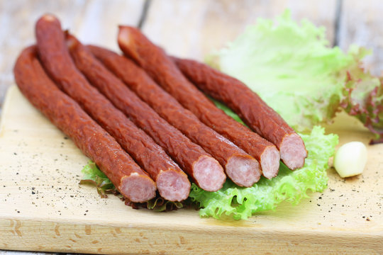 Traditional Polish smoked kabanos on lettuce on wooden board