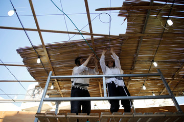 Ultra-Orthodox Jewish men build a ritual booth, known as a sukkah in Ashdod
