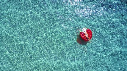 Luftaufnahme über eine schöne Frau mit Hut und weißem Bikini, die auf einer Luftmatzratze sich entspannt.