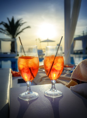 Two glasses with Aperol Spritz (aperitif cocktail consisting of prosecco, Aperol and soda water) near a swimming pool at sunset