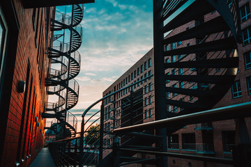 Spiral staircases in the old Warehouse District. Narrow canal and red brick buildings of Speicherstadt in Hamburg. After sunset