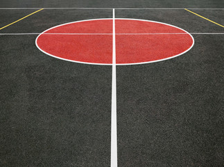 Perspective view of center circle of sports field with white lines. Black and red playing ground for games