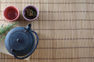 tea bowls and traditionnal asian teapot on a bamboo mat