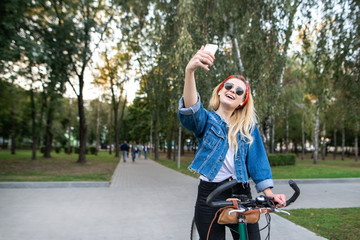 Happy attractive girl in the park with the bike to take selfie smartphone and smiles. Woman cyclist takes selfie with the bike in the park. Copyspace