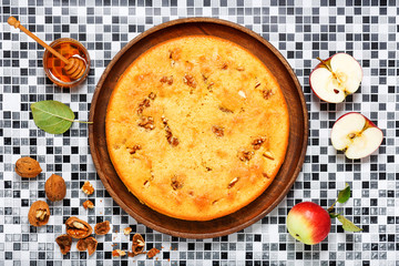 Homemade sponge cake with walnuts, cinnamon and apples. Top view. Culinary pastries.