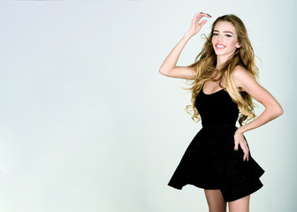 Sexy woman in black dress. Beauty, fashion, hairstyle. Girl with wavy hair. Elegant lady in black prom dress. Fashion woman in stylish little black dress. Elegant woman in black mini dress. Copy space