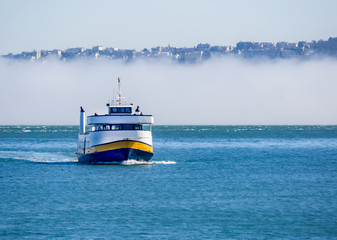 Ferry Boat on San Francisco Bay / A passenger ferry boat on the blue water of San Francisco Bay against a background of fog.