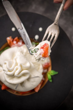 Whole tied Italian cheese burrata on small wooden plate served with fresh tomatoes and basil on dark textured background