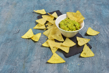 Mexican nachos chips with green guacamole sauce or dip in white bowl on black slate board