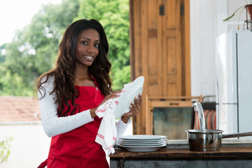 Beautiful african american housewife cleaning dishes