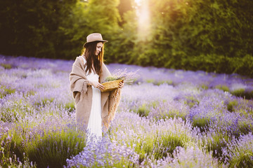 Woman holding basket with lavender flowers while standing at farm