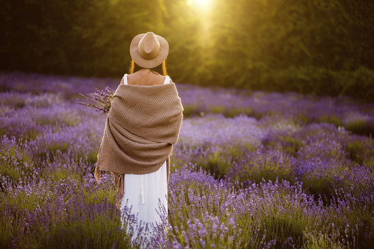 Rear view of woman standing in lavender flowers field during sunset