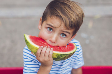 Close-up portrait of boy eating watermelon while sitting outdoors