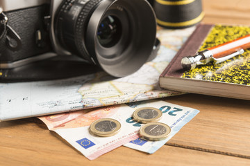 Camera, map, notebook, ball pen and money on wooden table