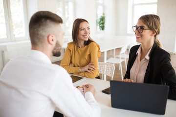 Two cheerful business women happily talking with male applicant for work. Young smiling employers spending job interview in office