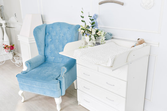 Blue chair and changing table for infants. interior of a spacious children's room.