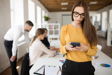 Beautiful business woman in eyeglasses using cellphone in office with colleagues on background