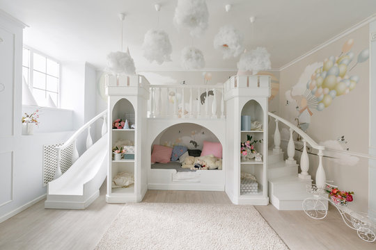 interior of a spacious children's room. decorative castle with bed inside, game slide and stairs