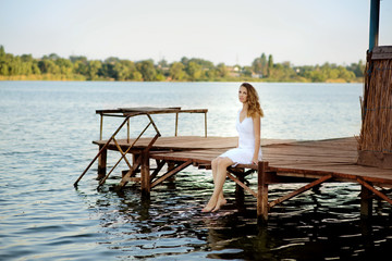 The young beautiful girl sits on a pier on the bank of the lake, having lowered legs in water