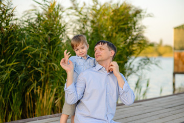 Happy father and the son sit on a pier on the bank of the lake
