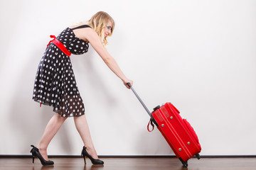 woman pulling heavy red travel bag
