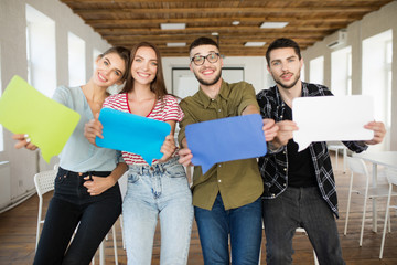 Group of young joyful people showing colorful papers messages icons in hands happily looking in camera while spending time at work in modern office