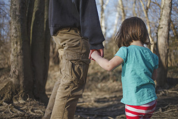 Midsection of father holding daughter's hand while standing in forest