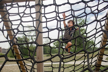 Boy climbing jungle gym against cloudy sky at playground