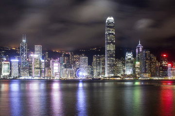 Illuminated modern buildings against cloudy sky reflecting on Hong Kong Island at night