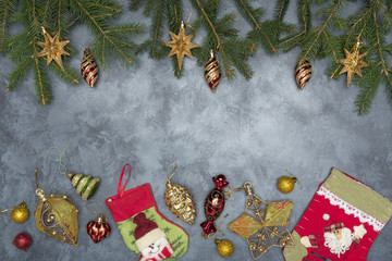 Holiday frame of Christmas decorations on blue dark stucco concrete background with fir branch, gold balls, stars, Christmas socks and toys. Elegant New Year`s snowy card. Top view.