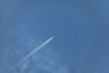 aircraft with contrail in morning sun