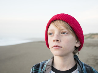 Close-up of thoughtful boy looking away while standing at beach against clear sky