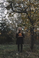 Young woman holding jack o' lantern while standing in forest during Halloween