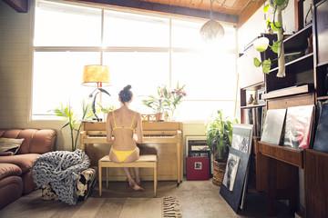 Rear view of woman wearing bikini while playing piano at home