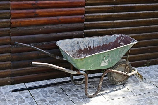 A wheelbarrow and a rake. This photo can be used to represent the concept of labor or garden maintenance.