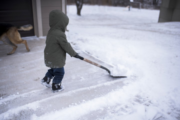 Side view of boy removing snow with shovel on driveway
