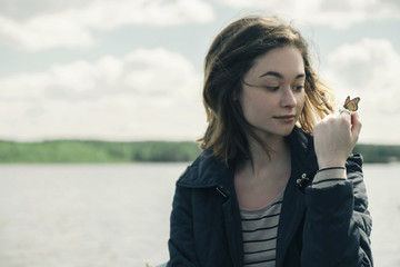 Woman holding butterfly while sitting by lake against cloudy sky