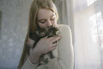 Young woman carrying kittens while standing at home
