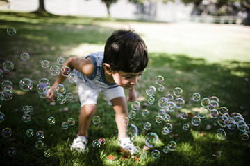 High angle view of boy playing with bubbles while standing on grassy field at park