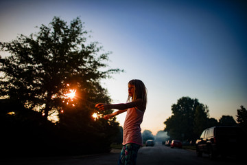 Girl holding burning sparklers while standing on street against clear blue sky during sunset