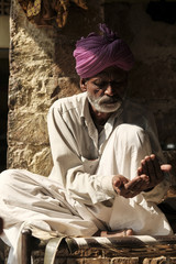 Man wearing traditional clothing while sitting on charpai by wall