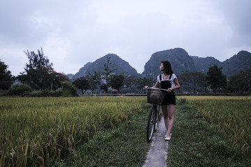 Woman with bicycle walking on field against mountains