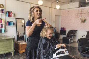 Cheerful hairdresser combing girl's hair in salon