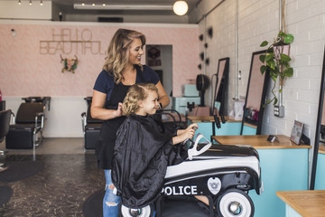 Smiling hairdresser cutting girl's hair while standing in salon