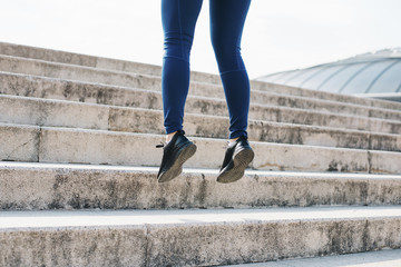 Low section of mid adult woman hopping on concrete steps while exercising at park during sunny day