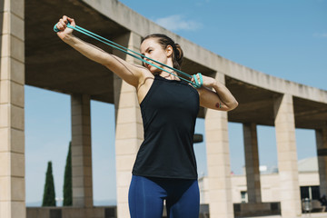 Mid adult woman stretching resistance band while exercising on pavement at park during sunny day