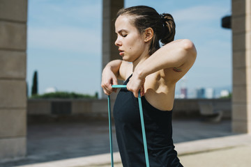 Mid adult woman pulling resistance band while exercising on pavement at park