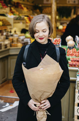 Woman with eyes closed holding bouquet while standing against market stall in city