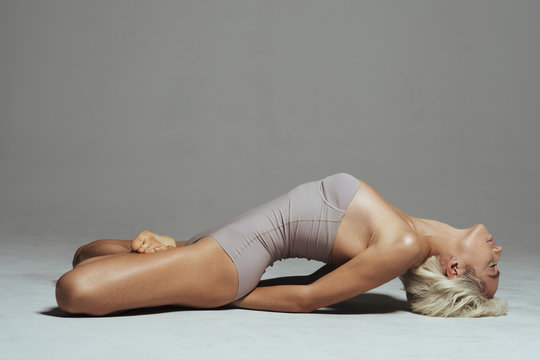 Side view of woman meditating while lying on floor